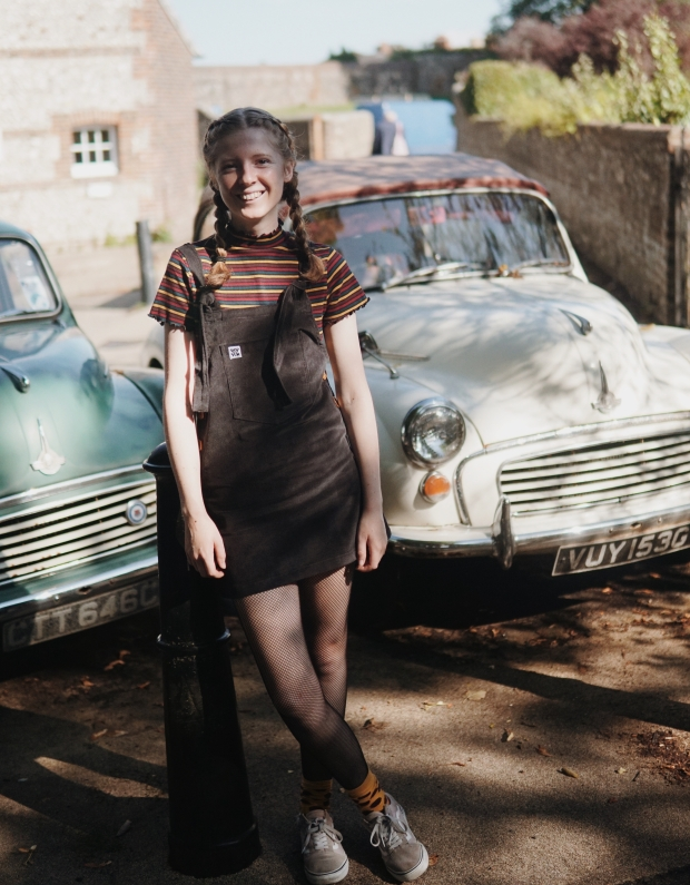 potrait of girl in dungarees dress with vintage cars, lewes