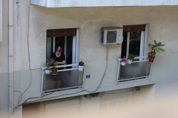 woman watering plants out window in greece, athens
