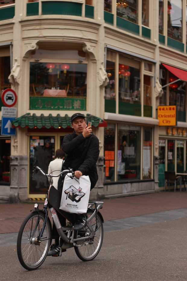 cycling man taking a photo on his phone in Amsterdam
