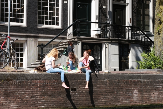 three women sitting by canal in Amsterdam