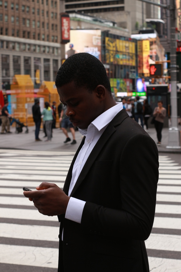 smart man in suit checking his phone in new york