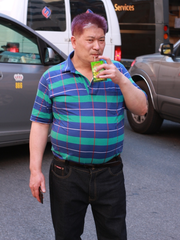 man drinking juice in chinatown, new york