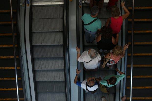 people on one side of escalator